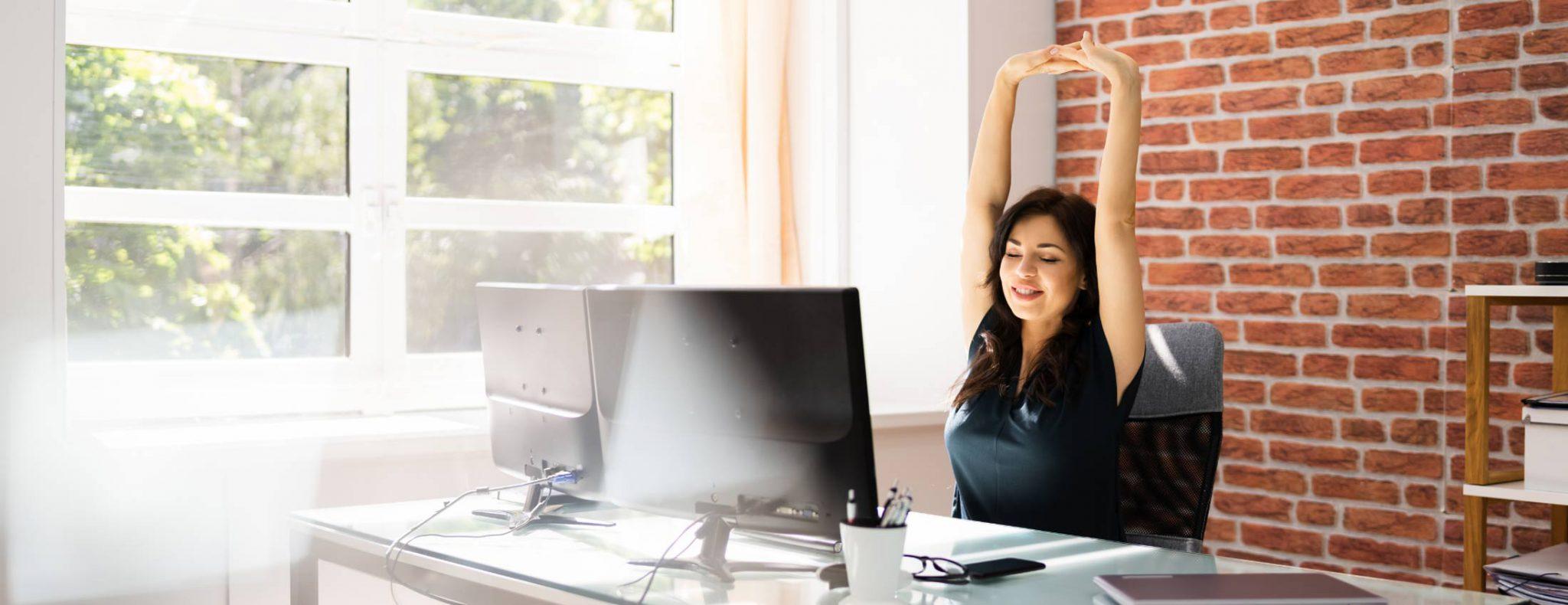 photo d'une employée de bureau qui fait des étirements pour éviter les risques physiques au travail